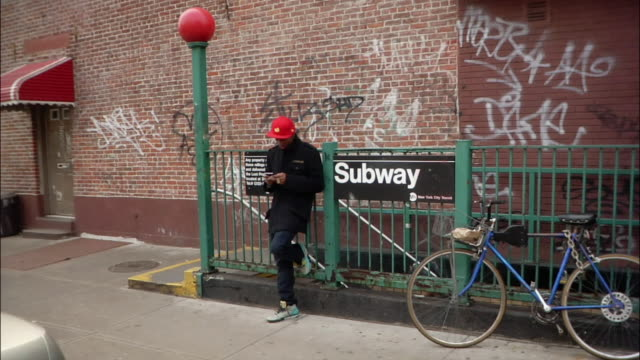 Wide shot Young man waiting and using electronic organizer, then giving brother street handshake and walking past subway sign / New York City, New York, USA