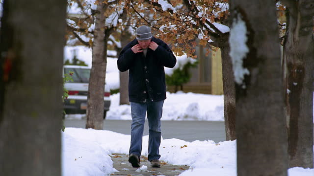 Wide shot young man walking on sidewalk and blowing on hands with snow falling on him from tree branch / Utah