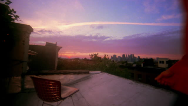 Wide shot young man walks to chair on roof at sunset / sits down with hands behind head / New York City