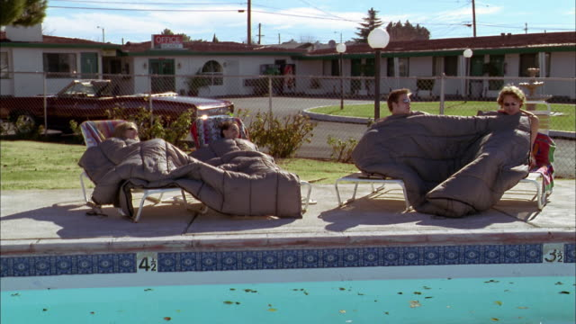 wide shot young men and women reclining in sleeping bags on lounge chairs by motel swimming pool - 寝袋点の映像素材/bロール