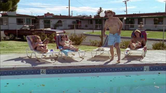 wide shot young people reclining on lounge chairs beside motel swimming pool / testing water - sunbathing stock videos & royalty-free footage