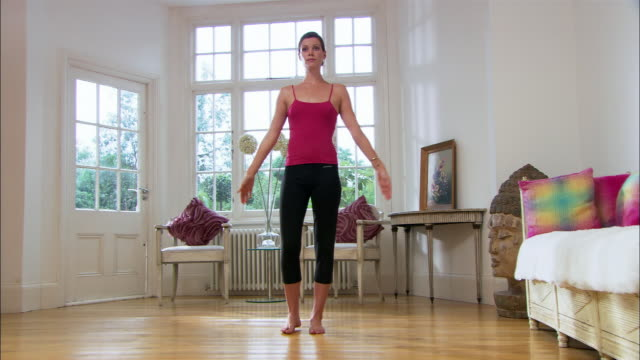 wide shot young woman doing yoga in living room/ london - nur junge frauen stock-videos und b-roll-filmmaterial