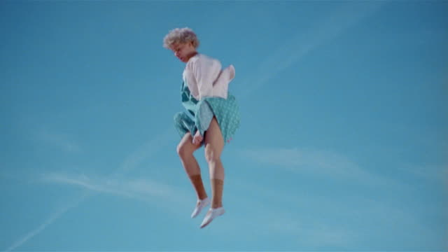 Wide shot young woman dressed as old woman jumping on trampoline