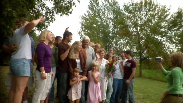 wide shot young woman filming large group of people at family reunion/ oshkosh, wisconsin, usa - family reunion stock videos and b-roll footage