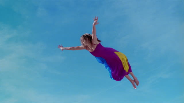 Wide shot young woman in colorful dress jumping on trampoline and assuming a diving position