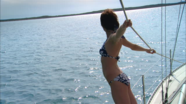 stockvideo's en b-roll-footage met wide shot young woman leaning on rope on sailboat deck/ harbor island, bahamas - haarband