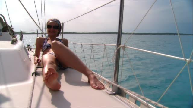 Wide shot Young woman sunbathing on sailboat deck/ Harbor Island, Bahamas
