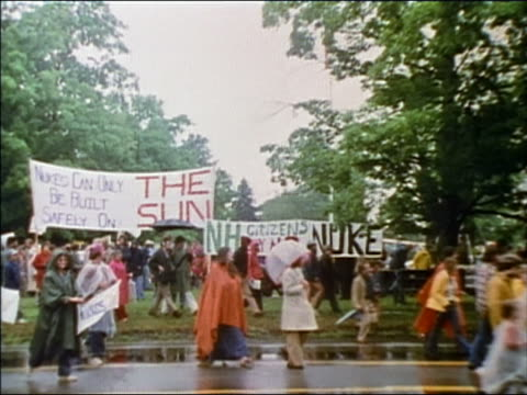 1976 wide shot zoom in antinuclear activists demonstrating in the rain / AUDIO / New Hampshire