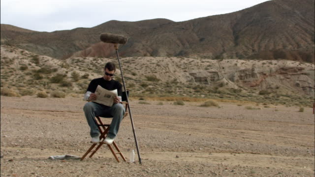 Wide shot zoom in boom operator taking a break and reading a newspaper on desert film set / Red Rock Canyon State Park, California