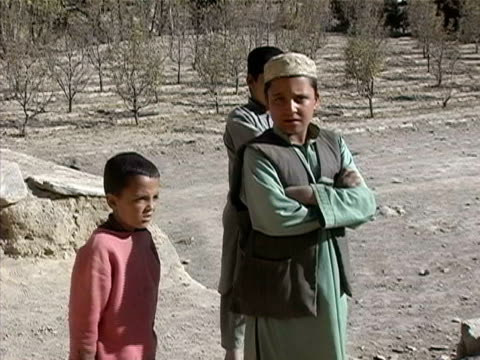 vídeos de stock, filmes e b-roll de wide shot zoom in boys looking at camera/ pan armed soldier standing by/ afghanistan - uniforme militar