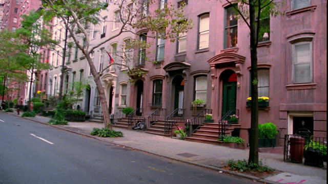 Wide shot zoom in brownstone apartment buildings with trees in front / Manhattan, New York City