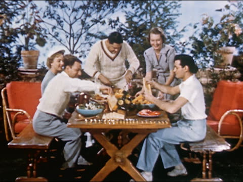 1951 wide shot zoom in close up man carves turkey for group of people seated at food-covered picnic table / audio - social grace stock videos & royalty-free footage