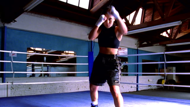 wide shot zoom in female boxer facing camera shadow boxing with taped hands in ring