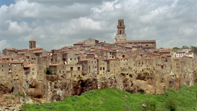 Wide shot zoom in houses in hillside town of Pitigliano / bell tower in background / Tuscany, Italy