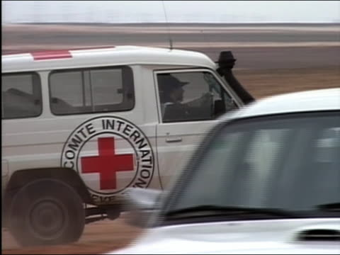wide shot zoom in international committee red cross van riding past men / iraq - red cross stock videos & royalty-free footage
