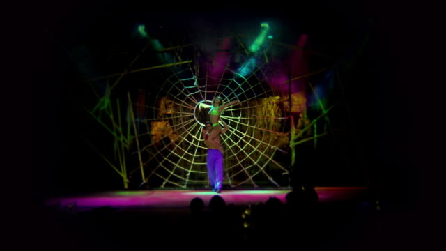 wide shot zoom in man with woman on shoulders performing on stage / large spider web + waterfall in background - stage costume stock videos & royalty-free footage