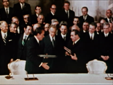 vídeos de stock e filmes b-roll de 1974 wide shot zoom in president nixon and leonid brezhnev exchanging books and shaking hands - leonid brezhnev