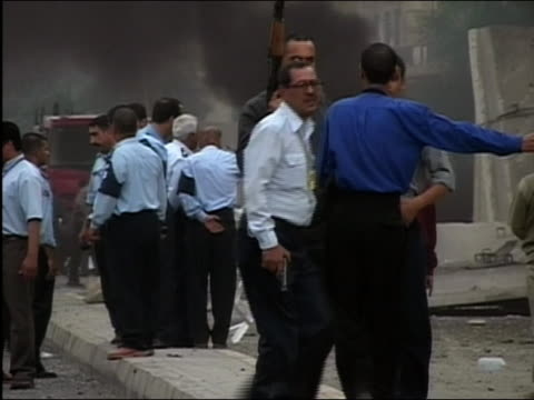 2003 wide shot zoom in soldiers and policemen near the scene of a car bombing / baghdad iraq - 2003年点の映像素材/bロール