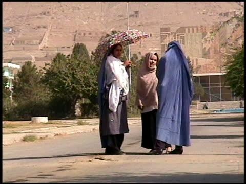 vidéos et rushes de 2002 wide shot zoom in three women talking in street / mountain in background / afghanistan - châle