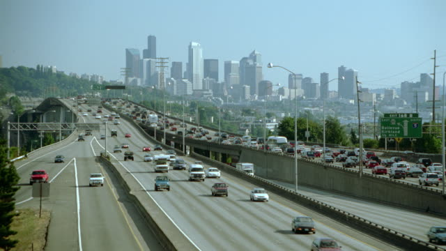 wide shot zoom in traffic on highway (interstate 5) in front of seattle skyline / washington - seattle stock videos & royalty-free footage