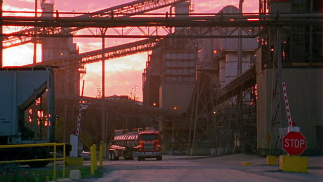 wide shot zoom in truck driving on factory lot at sunset - haulage stock videos & royalty-free footage