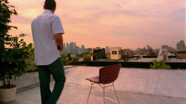 wide shot zoom in young man walking to chair on rooftop / sitting down and drinking beer / nyc skyline in background - 飲む点の映像素材/bロール