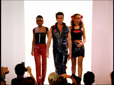 stockvideo's en b-roll-footage met wide shot zoom in zoom out 3 models in leather and vinyl clothing walking on catwalk with audience in foreground (speed change) - catwalk toneel