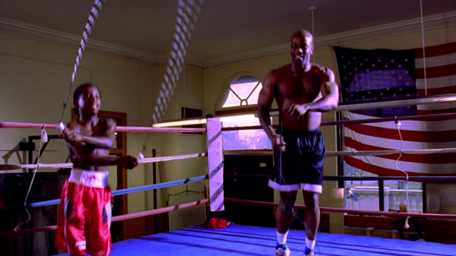 wide shot zoom in zoom out PAN Black male boxer + young boy jumping rope in boxing ring with American flag in background