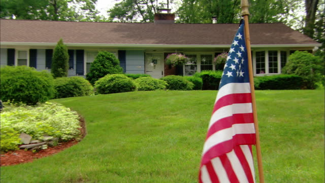 Wide shot zoom out American flag flapping in the breeze on front lawn of suburban ranch house