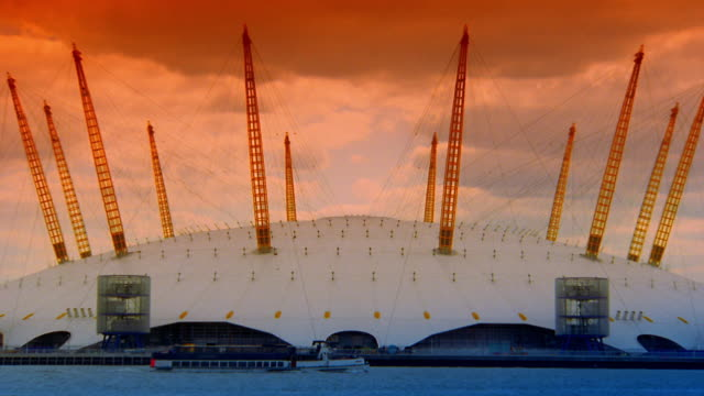 Wide shot zoom out boat passing Millennium Dome on Thames River / London