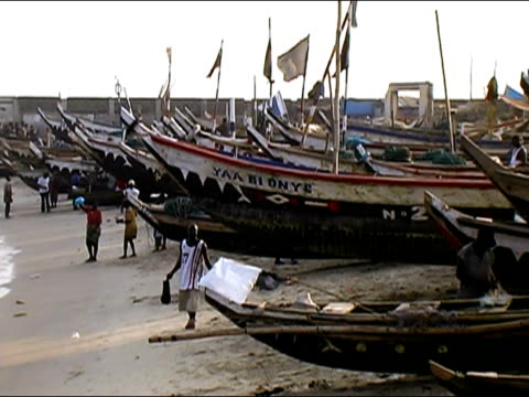 Wide shot zoom out boats on sand along beach/ Ghana