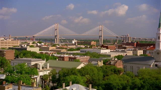 Wide shot zoom out buildings of Savannah with Talmadge Memorial Bridge in background / Georgia