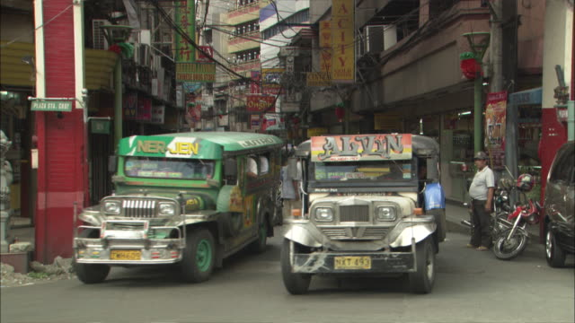 wide shot zoom out - colorful jeepney taxis driving on a narrow city street / manilla philippines - philippines stock videos & royalty-free footage