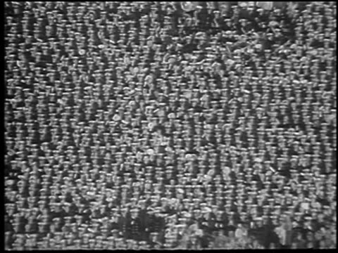 B/W 1965 wide shot zoom out crowd of Navy students cheering at Army vs Navy football game / Philadelphia / news