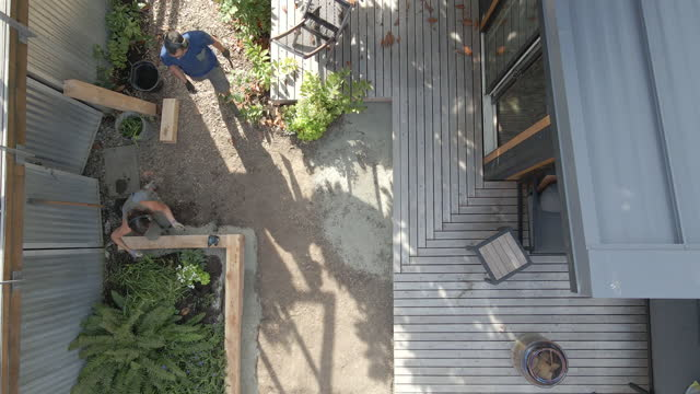 wide shot zoom out drone view of couple building garden beds in backyard on summer afternoon - diy stock videos & royalty-free footage