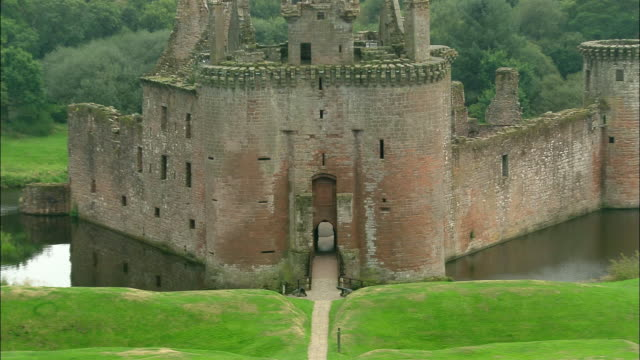 wide shot zoom out entrance and footbrige to caerlaverock castle/ aerial wide shot pan overhead view of castle and moat/ dumfries and galloway, scotland - scottish culture bildbanksvideor och videomaterial från bakom kulisserna