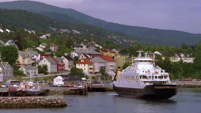 wide shot zoom out ferry pulling into dock of coastal village / norway - ferry stock videos & royalty-free footage