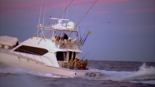 stockvideo's en b-roll-footage met wide shot zoom out man on fishing boat pulling in fish while surrounded by friends/ zoom in men on boat/ long beach, california - noordelijke grote oceaan