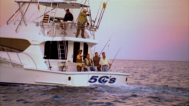 stockvideo's en b-roll-footage met wide shot zoom out man on fishing boat pulling in fish while surrounded by friends/ long beach, california - noordelijke grote oceaan