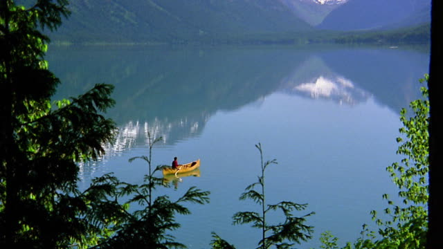 wide shot zoom out man paddling canoe in lake / mountains in background - sparklondon stock videos and b-roll footage