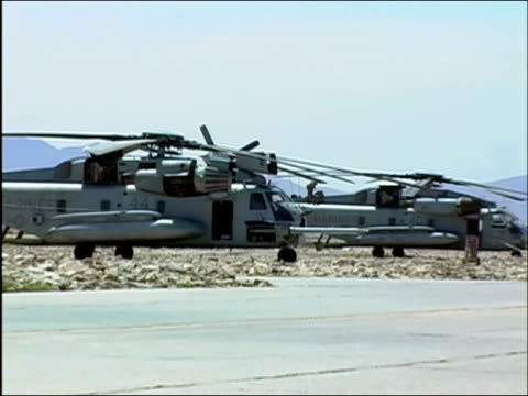 stockvideo's en b-roll-footage met wide shot zoom out military helicopters parked near runway at bagram air base / bagram afghanistan / audio - bagram air base