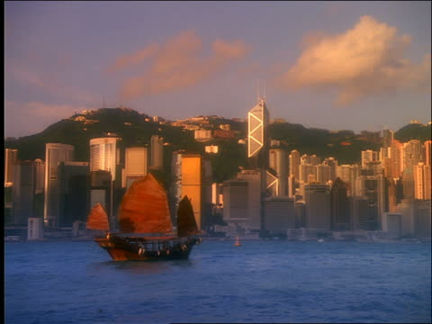 wide shot zoom out of junk in harbor with hong kong skyline in background / central district / diffusion filter - central district hong kong stock videos & royalty-free footage