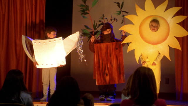 wide shot zoom out pan children in costume for school play with sun dancing across stage and audience watching in foreground - theatrical performance stock videos & royalty-free footage