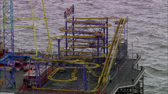 wide shot zoom out rollercoaster on pier/ blackpool, england - blackpool stock-videos und b-roll-filmmaterial