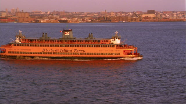wide shot zoom out staten island ferry traveling in ny harbor w/manhattan skyline in background - new york harbor stock videos & royalty-free footage