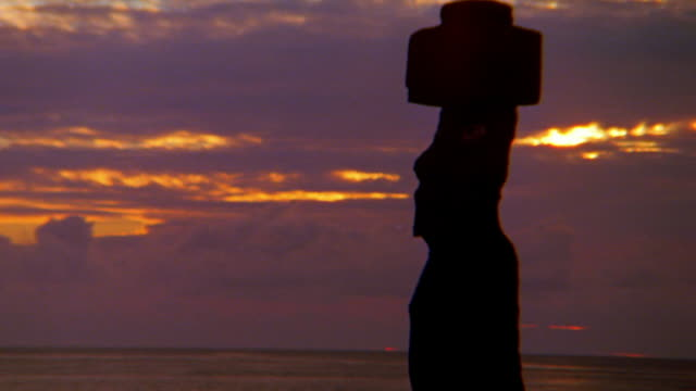 wide shot zoom out stone moai statue on easter island with pacific ocean in background at dusk / south pacific - south pacific ocean stock videos and b-roll footage
