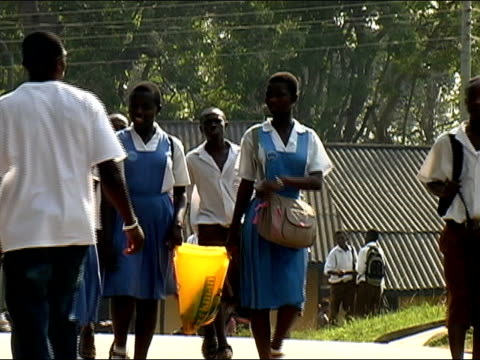 Wide shot zoom out teenagers walking on street in school  uniforms/ Ghana