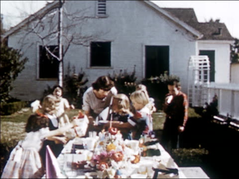 1954 wide shot zoom out young girls coming out of hiding and running towards birthday girl at outdoor surprise party / placing gifts in her arms / audio - 1954 stock videos & royalty-free footage