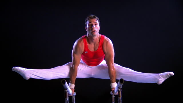 wide shot zoom out zoom in male gymnast peforming routine on parallel bars - doing the splits stock videos & royalty-free footage