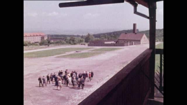 wide shot, zooming out to show tourists visiting buchenwald concentration camp; 1970. - horizon over land stock videos & royalty-free footage